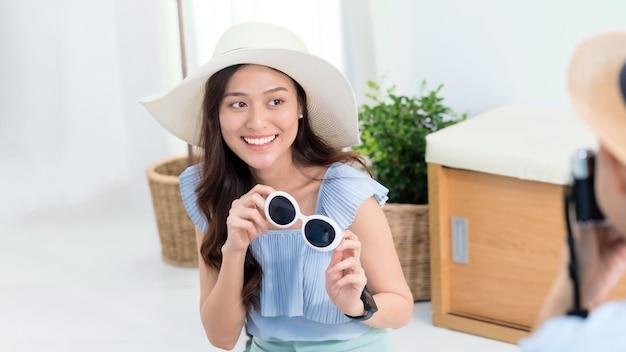 Casal de turistas asiáticos planejando informações sobre viagens e tirando fotos para viajar antes da data da viagem em casa, segundo plano.