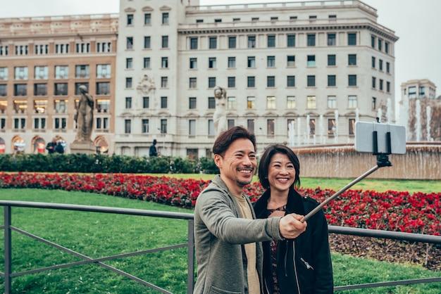 Casal de turistas asiáticos tomando uma selfie no telefone celular