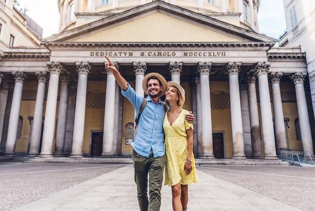 Casal de turistas caminhando na cidade de milão, itália - pessoas que visitam roma