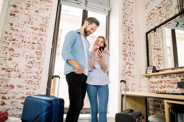 Casal de turistas com bagagem pronta para viajar, reservar os bilhetes on-line usando telefone celular