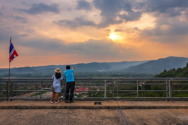 Casal de turistas de com excelente vista para a vista do rio e as montanhas na barragem de khun dan prakan chon