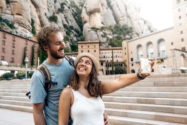Casal de turistas de férias tirando uma foto de selfie no mosteiro de montserrat, barcelona, espanha