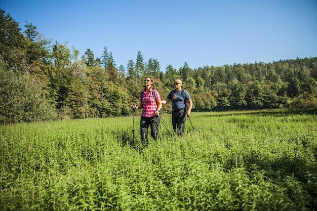 Casal de turistas em um caminho de terra em um parque natural em rakov skocjan, eslovênia