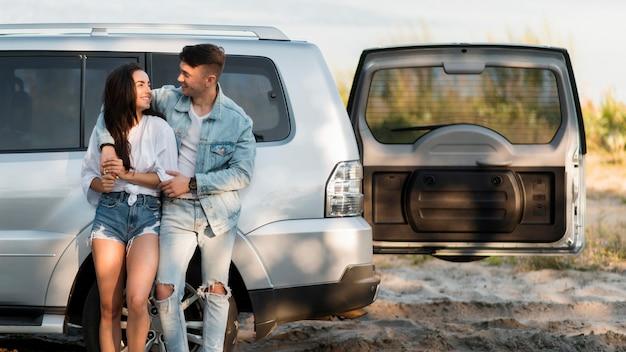 Casal de turistas felizes e seu carro