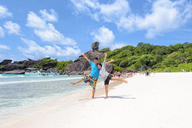 Casal de turistas levantou os braços e as pernas com felicidade na praia perto do mar, sob um céu azul e nuvens de verão na ilha de koh similan no parque nacional de mu ko similan, província de phang nga, tailândia