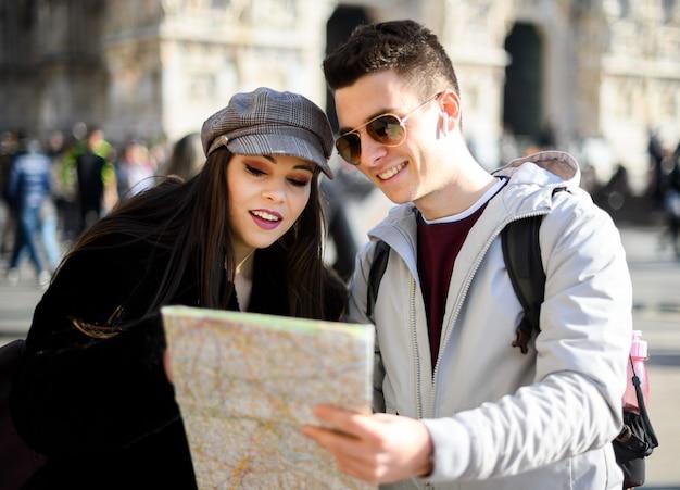 Casal de turistas na cidade, olhando para um mapa e discutindo sobre o próximo destino