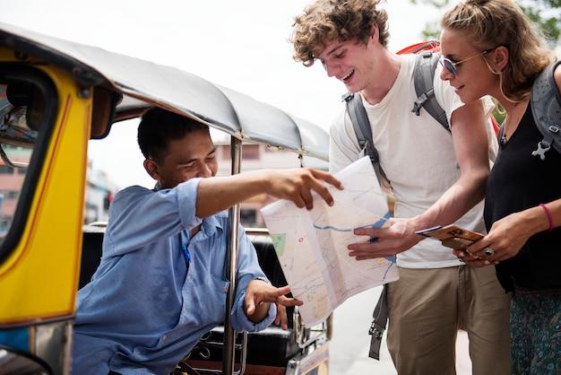 Casal de turistas pedindo tuk tuk motorista de táxi nativo para a direção