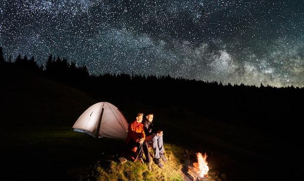 Casal de turistas perto da fogueira e tendas sob o céu noturno cheio de estrelas e via láctea