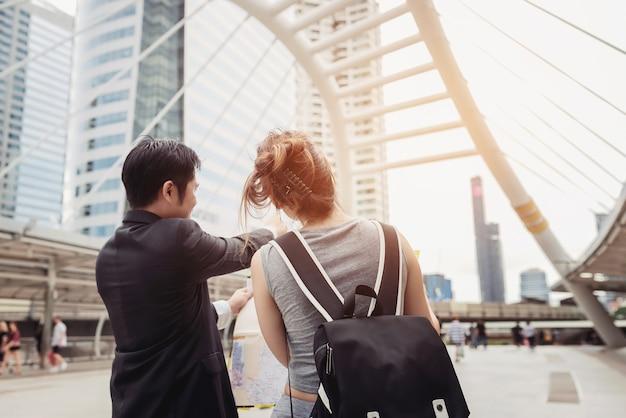 Casal de turistas procurando localização em um guia com um porto em segundo plano