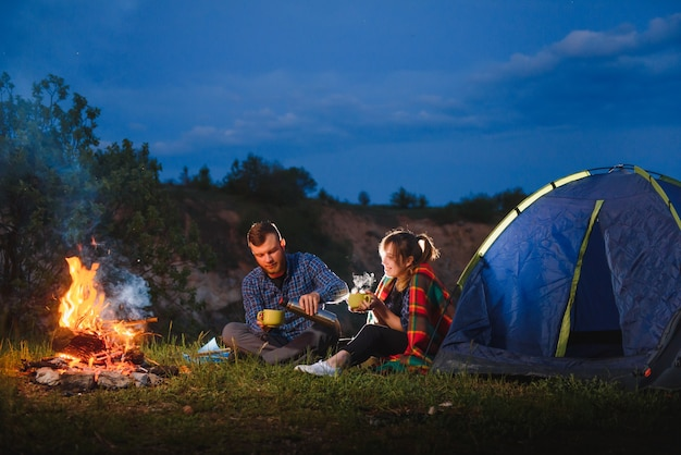Casal de turistas sentado em frente a uma barraca iluminada iluminada por uma fogueira
