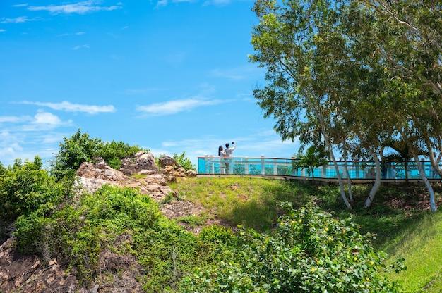 Casal de turistas tirando fotos em um mirante na montanha. há um lindo mar azul ao fundo.