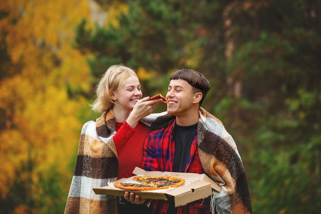Casal de um homem e uma mulher jovem engraçado bonito desfrutar de pizza e socializar em um piquenique na natureza juntos