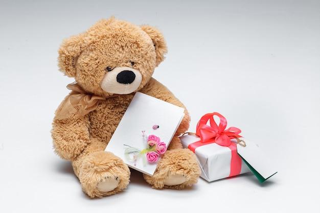 Casal de ursos de pelúcia com coração vermelho e presente em branco.