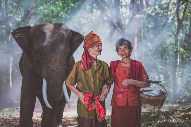 Casal de velhos andando com seu elefante na selva, na tailândia