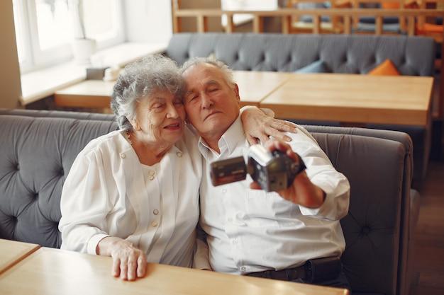 Casal de velhos elegantes em um café usando uma câmera
