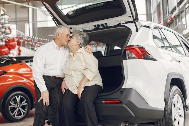 Casal de velhos elegantes em um salão de carro