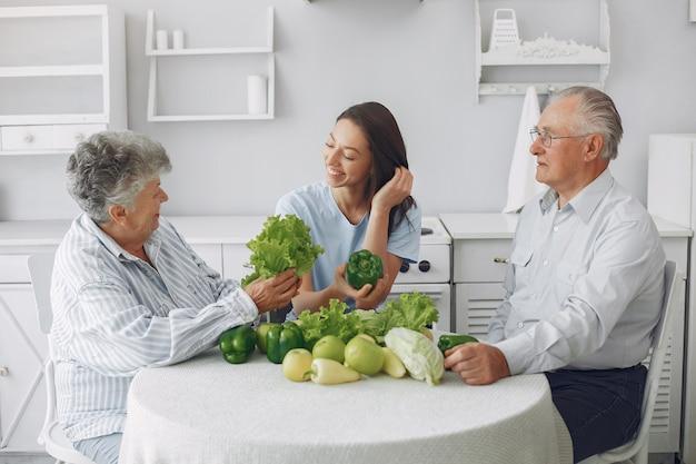 Casal de velhos em uma cozinha com jovem neta