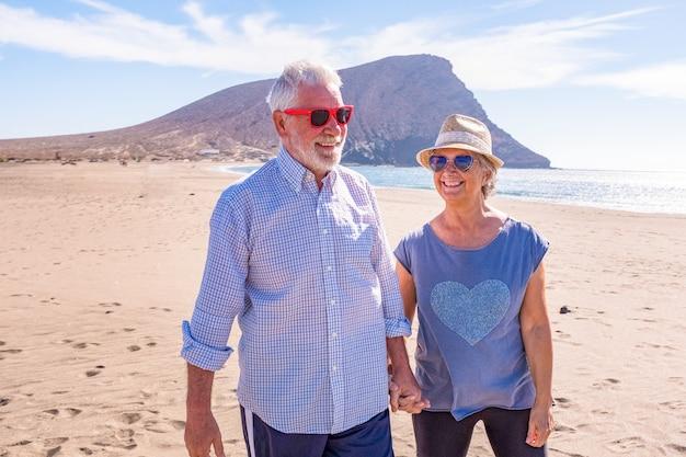 Casal de velhos se divertindo caminhando na areia da praia juntos curtindo