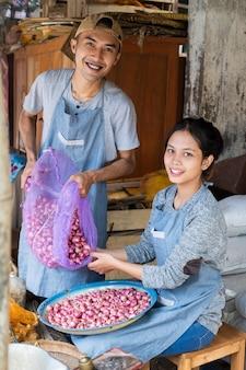 Casal de verdureiros sorriu enquanto puxava as chalotas do saco para a bandeja na barraca de legumes