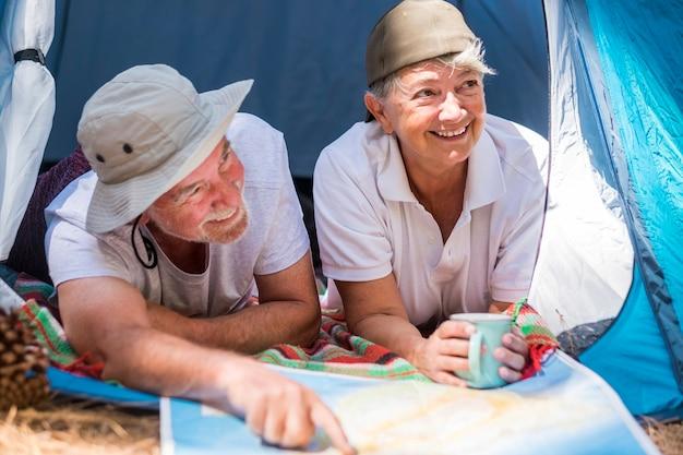 Casal de viajantes adultos caucasianos dentro de uma tenda em acampamento grátis - felicidade para pessoas alegres que adoram descobrir o mundo - estilo de vida com desejo de viajar para homens e mulheres aposentados - Foto Premium