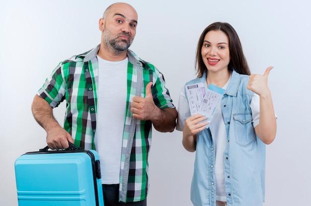 Casal de viajantes adultos confiante segurando uma mala e uma mulher sorridente segurando passagens, ambos mostrando o polegar para cima, olhando