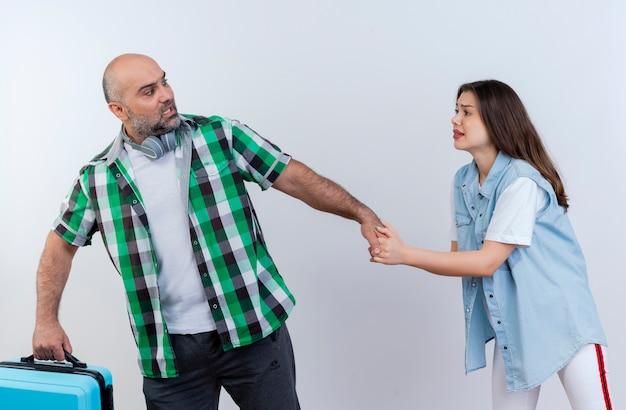 Casal de viajantes adultos descontentes com um homem usando fones de ouvido no pescoço segurando uma mala e uma mulher triste puxando sua mão implorando para ele, ambos olhando um para o outro isolados