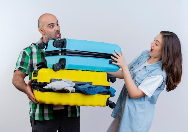 Casal de viajantes adultos impressionados segurando malas, mulher colocando a mão em um dos dois olhando para as malas