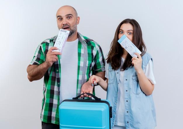 Casal de viajantes adultos impressionados segurando uma mala e ambos tocando o queixo com passagens e olhando