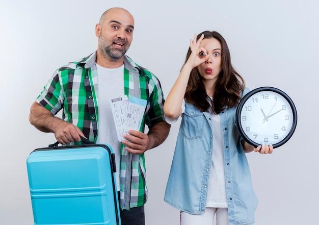 Casal de viajantes adultos impressionados segurando uma mala e bilhetes de viagem e uma mulher segurando um relógio e fazendo um gesto de olhar, ambos olhando