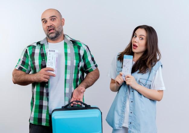 Casal de viajantes adultos impressionados segurando uma mala e os dois segurando passagens olhando
