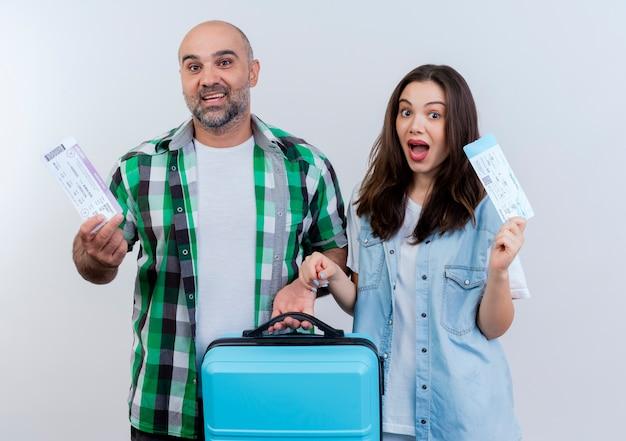 Casal de viajantes adultos impressionados segurando uma mala e segurando uma passagem olhando