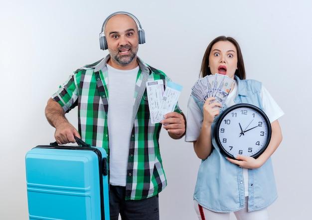 Casal de viajantes adultos impressionados usando fones de ouvido segurando bilhetes de viagem e uma mulher mala segurando dinheiro e relógio, ambos olhando