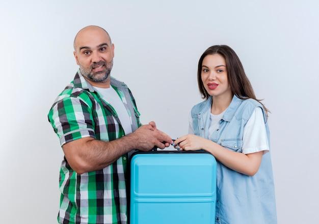 Casal de viajantes adultos satisfeitos, segurando uma mala e olhando