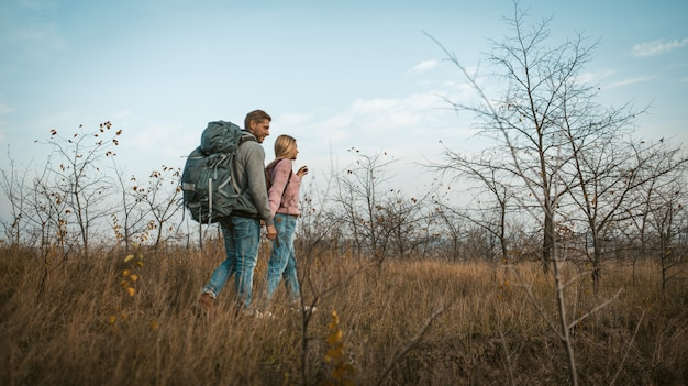 Casal de viajantes andando por um campo de outono de mãos dadas.