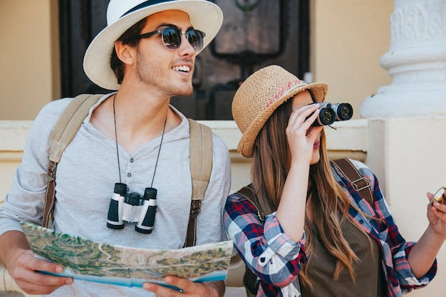 Casal de viajantes com binóculos, mapa e óculos de sol