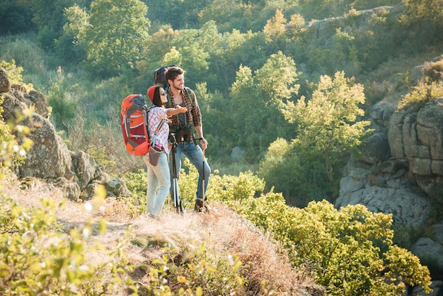 Casal de viajantes de corpo inteiro perto do desfiladeiro olhando para longe