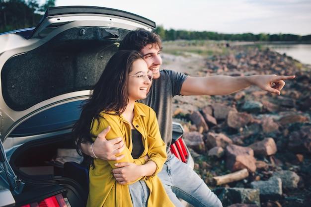 Casal de viajantes feliz sentado no porta-malas do carro aberto e assistir o nascer do sol.