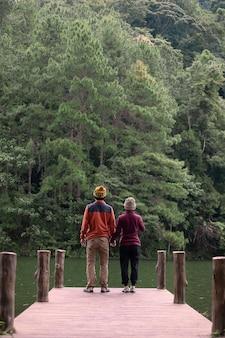 Casal de viajantes felizes em pé em um píer olhando para o rio e o fundo da floresta