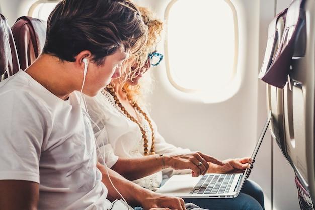 Casal de viajantes felizes, mãe e filho, sentam-se no avião, prontos para aproveitar o voo, com um laptop, computador pessoal e conexão à internet a bordo