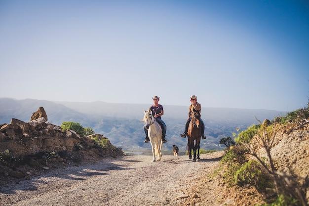 Casal de vida de caubói ao ar livre cavalga na montanha desfrutando de uma excursão na natureza - estilo de vida alternativo de viagens de férias para pessoas