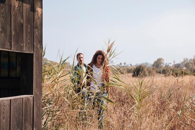 Casal de vista frontal andando em um campo de trigo