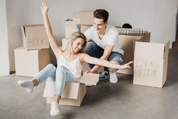 Casal de vista frontal brincando com caixas de papelão