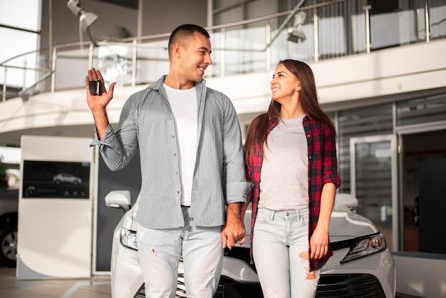 Casal de vista frontal na concessionária de carros