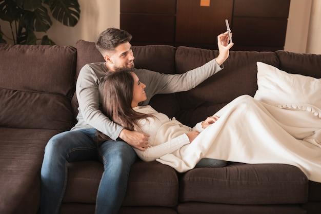 Casal de vista frontal no sofá tomando selfie