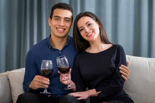 Casal de vista frontal tomando uma taça de vinho enquanto está sentado no sofá