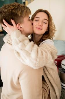 Casal de vista lateral beijando