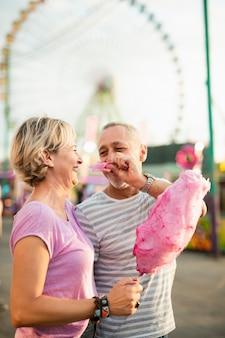 Casal de vista lateral com algodão doce rosa
