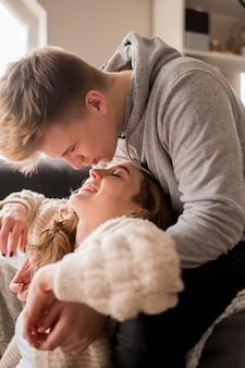 Casal de vista lateral em casa beijando