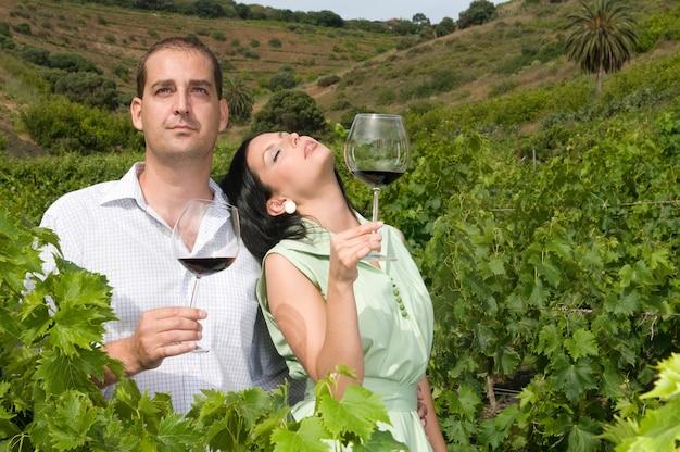 Casal degustando vinho de suas adegas em um vinhedo