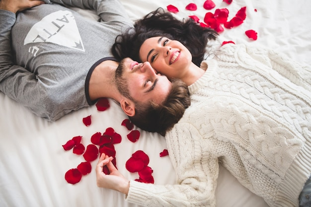 Casal deitado na cama cabeça com cabeça cercado por pétalas de rosa